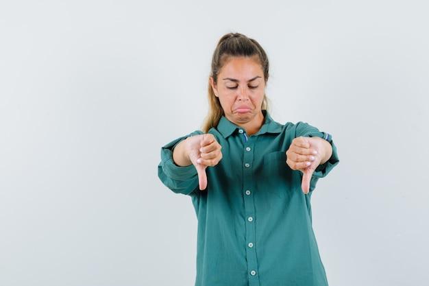 Młoda kobieta pokazuje kciuki w dół obiema rękami, krzywiąc się w zielonej bluzce i patrząc smutno