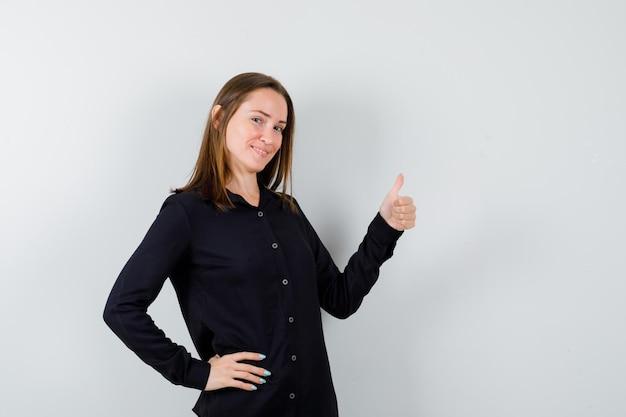 Młoda kobieta pokazuje kciuki w górę i wygląda na szczęśliwą
