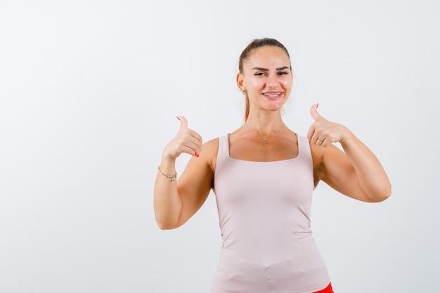 Młoda kobieta pokazuje kciuki w górę w podkoszulku i wygląda na szczęśliwą. przedni widok.