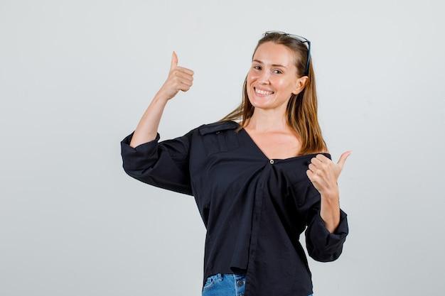 Młoda kobieta pokazuje kciuki w koszulę, spodenki, okulary i wesoły wyglądający
