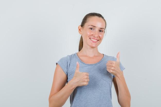 Młoda kobieta pokazuje kciuki w szarej koszulce i wygląda na szczęśliwą. przedni widok.