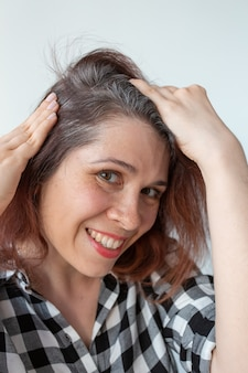 Młoda kobieta pokazuje koncepcję wczesnego starzenia się jej siwych włosów