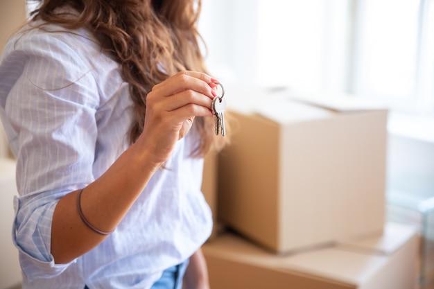 Młoda kobieta pokazuje lub daje klucz, pozowanie w nowym mieszkaniu z sterty kartonów w tle