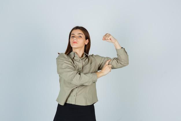 Młoda kobieta pokazuje mięśnie ramion w koszuli, spódnicy i wygląda pewnie
