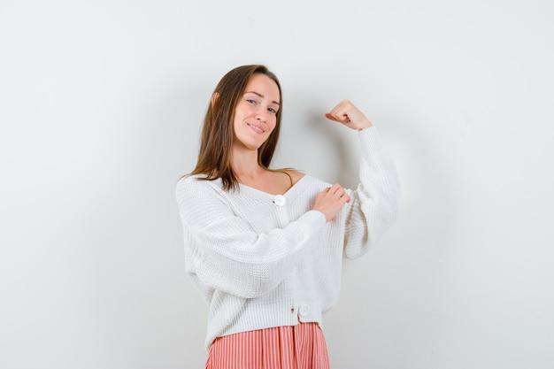 Młoda kobieta pokazuje mięśnie ramion w sweter i spódnicę, patrząc dumnie na białym tle