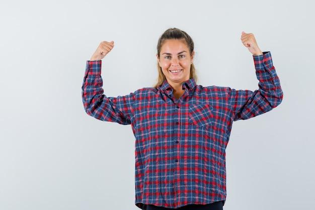 Młoda kobieta pokazuje mięśnie w kraciastej koszuli i wygląda potężnie