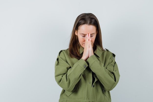 Młoda kobieta pokazuje modlący się gest w zielonej kurtce i szuka nadziei. przedni widok.