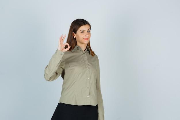 Młoda kobieta pokazuje ok gest w koszuli, spódnicy i wygląda pewnie