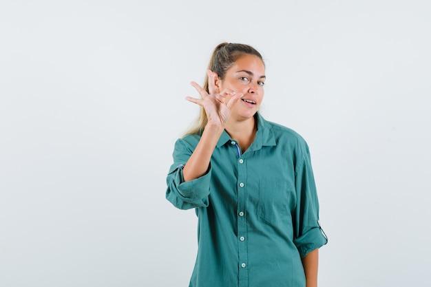 Młoda kobieta pokazuje ok gest w niebieskiej koszuli i szuka zadowolony