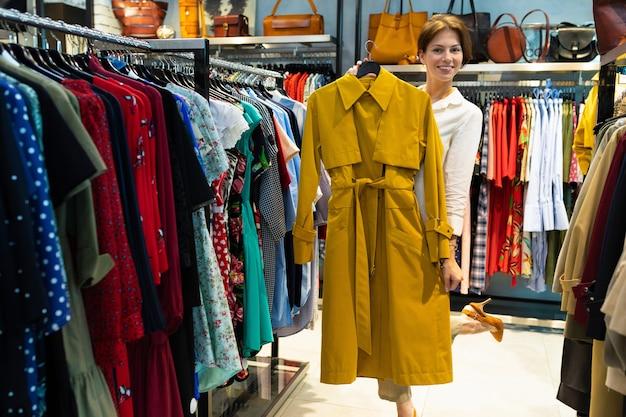 Młoda kobieta pokazuje płaszcz przeciwdeszczowy koloru musztardy w sklepie z ubraniami dla kobiet