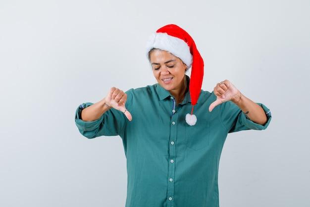 Młoda kobieta pokazuje podwójne kciuki w dół w koszuli, kapeluszu santa i patrząc wesoło, widok z przodu.