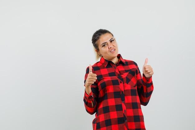 Młoda kobieta pokazuje podwójne kciuki w kraciastej koszuli i szuka szczęścia. przedni widok.