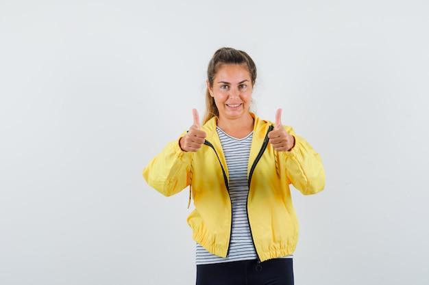 Młoda kobieta pokazuje podwójne kciuki w kurtce, t-shirt i wygląda pewnie. przedni widok.