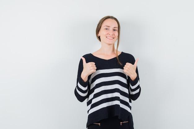 Młoda kobieta pokazuje podwójne kciuki w pasiastej dzianinie i czarnych spodniach i wygląda na szczęśliwą