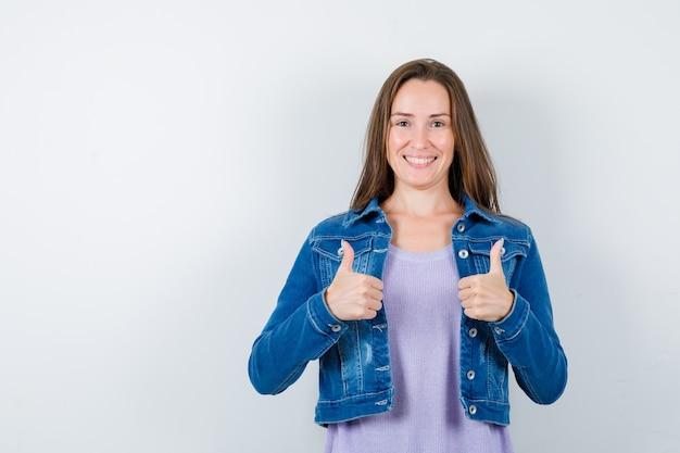 Młoda kobieta pokazuje podwójne kciuki w t-shirt, kurtkę i patrząc zadowolony, widok z przodu.