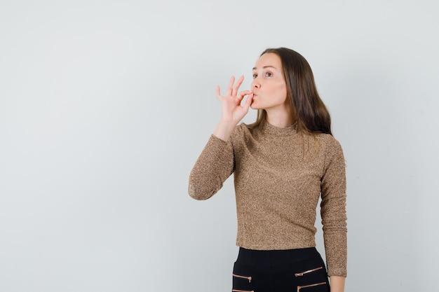 Młoda kobieta pokazuje pyszny gest w pozłacanym swetrze i czarnych spodniach i wygląda optymistycznie. przedni widok.