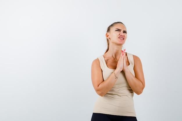 Młoda kobieta pokazuje splecione dłonie w błagalnym geście w beżowym podkoszulku i wygląda z nadzieją, widok z przodu.