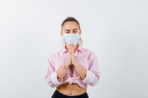 Młoda kobieta pokazuje splecione dłonie w błagalnym geście w koszuli, spodniach, masce medycznej i patrząc z nadzieją, widok z przodu.