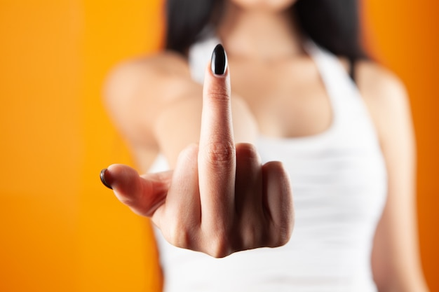 Młoda kobieta pokazuje środkowy palec na pomarańczowym tle