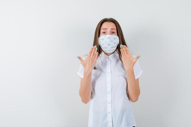 Młoda kobieta pokazuje swoją medyczną maskę i wygląda na zaniepokojoną