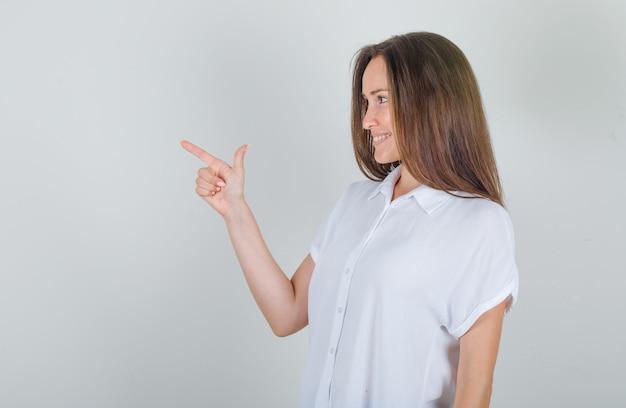 Młoda kobieta pokazuje symbol broni i uśmiecha się w białej koszuli.