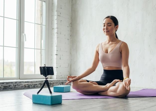 Młoda kobieta pokazuje technikę medytacji na nowy vlog