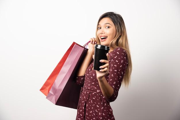 Młoda kobieta pokazuje torby sklepowe i filiżankę napoju na białej ścianie.
