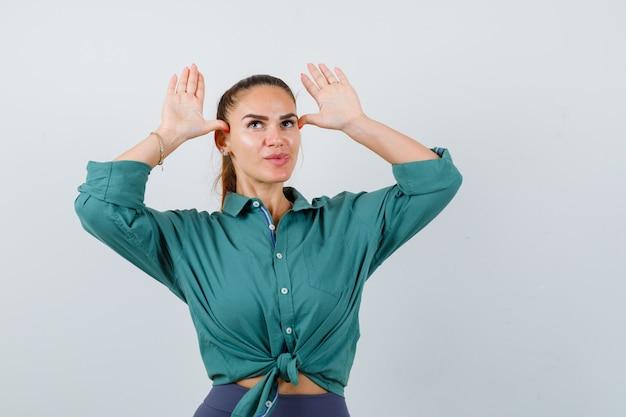 Młoda kobieta pokazuje uszy gest nad głową w zielonej koszuli i wygląda zabawnie. przedni widok.