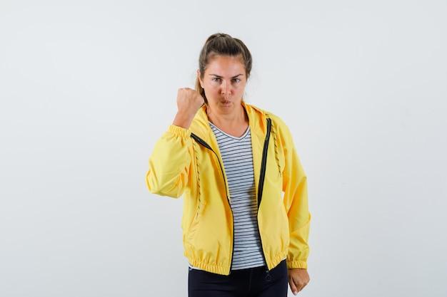 Młoda kobieta pokazuje zaciśniętą pięść w kurtce, t-shircie i wygląda pewnie. przedni widok.