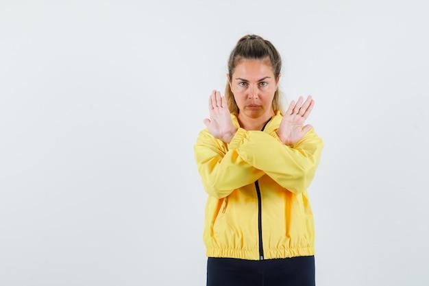 Młoda kobieta pokazuje zamknięty gest w żółtym płaszczu przeciwdeszczowym i wygląda poważnie