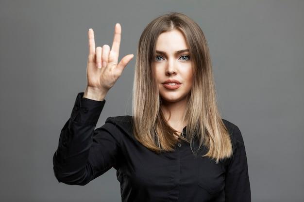 Młoda kobieta pokazuje znak kozy ręką. piękna blondynka w czarnej koszuli. symbol masoński, światowa teoria spiskowa. szare tło.