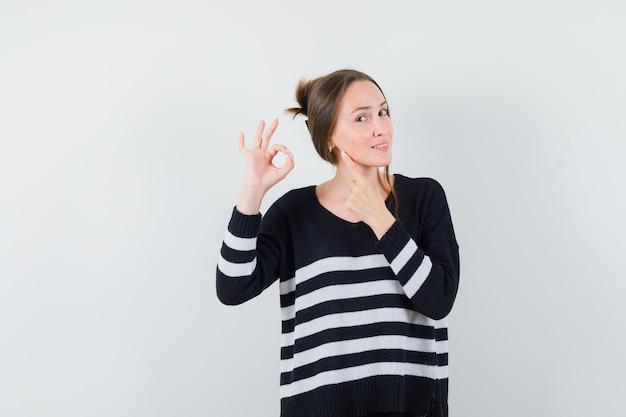 Młoda kobieta pokazuje znak ok i rozciągając palec wskazujący w dzianinie w paski i czarne spodnie i wygląda na szczęśliwą