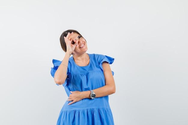 Młoda kobieta pokazuje znak ok na oko w niebieskiej sukience i patrząc wesoło