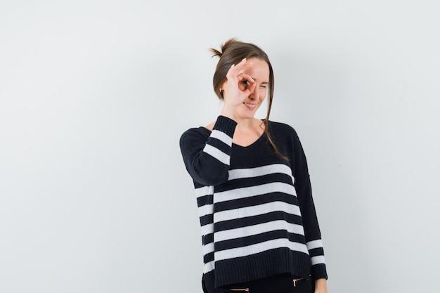Młoda kobieta pokazuje znak ok nad okiem i mruga w dzianinie w paski i czarnych spodniach i wygląda na szczęśliwą