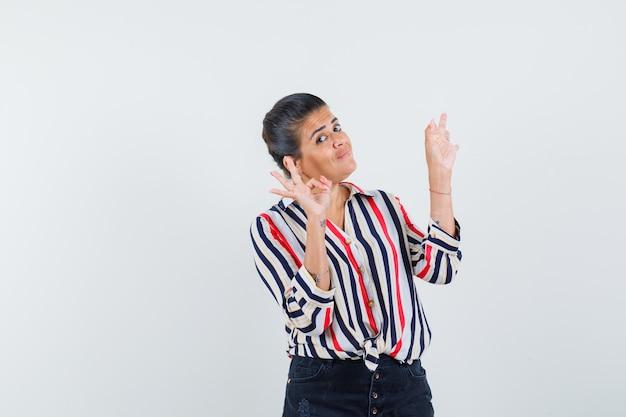 Młoda kobieta pokazuje znak ok obiema rękami w bluzce w paski i wygląda optymistycznie