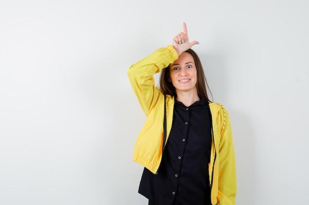 Młoda kobieta pokazuje znak przegranego