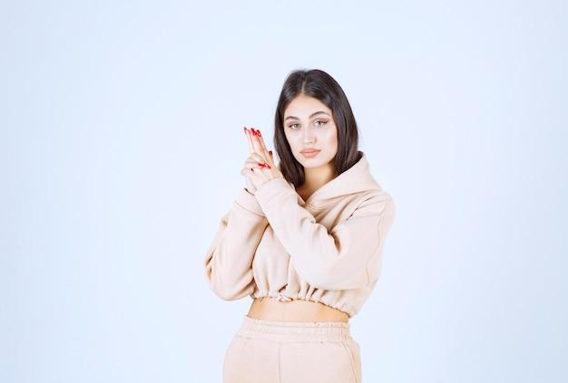 Młoda kobieta pokazuje znak ręką pistolet