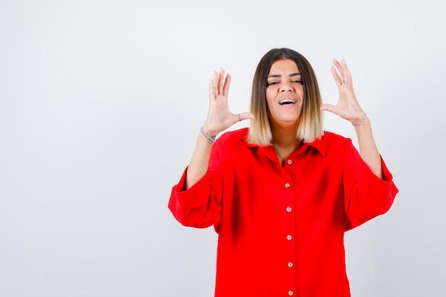 Młoda kobieta pokazuje znak rozmiaru w czerwonej koszuli oversize i wygląda pewnie, widok z przodu.