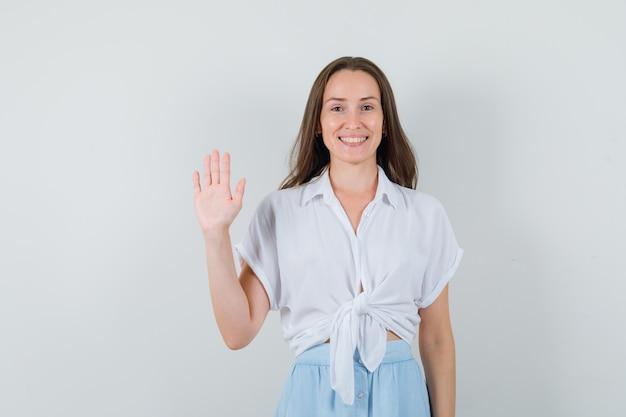 Młoda kobieta pokazuje znak stop w białej bluzce i jasnoniebieskiej spódnicy i wygląda wesoło