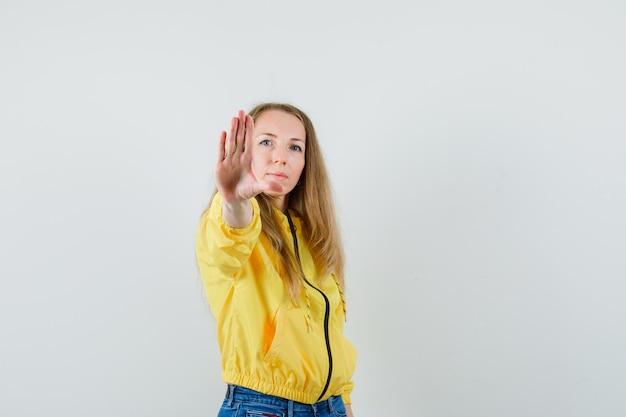 Młoda kobieta pokazuje znak stopu w żółtej kurtce bomber i dżinsach i wygląda poważnie, widok z przodu.