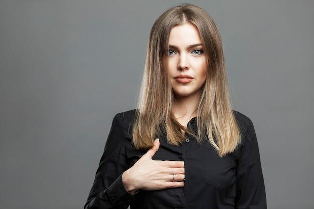 Młoda kobieta pokazuje znak ukrytej dłoni. piękna blondynka w czarnej koszuli. symbolika masońska i teoria spisku światowego. szare tło.