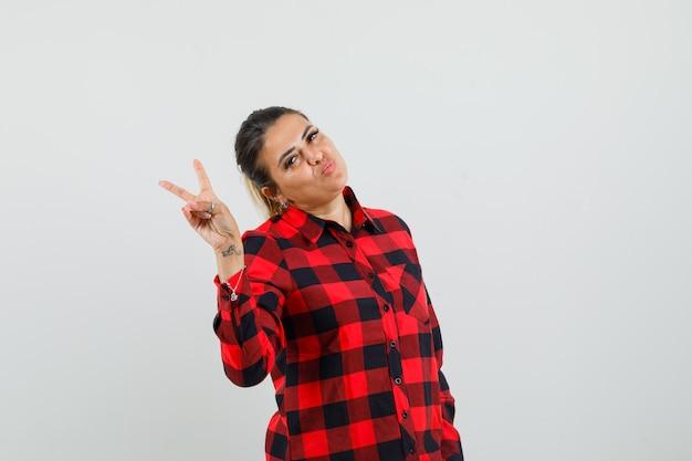 Młoda kobieta pokazuje znak v w kraciastej koszuli i wygląda pewnie, widok z przodu.