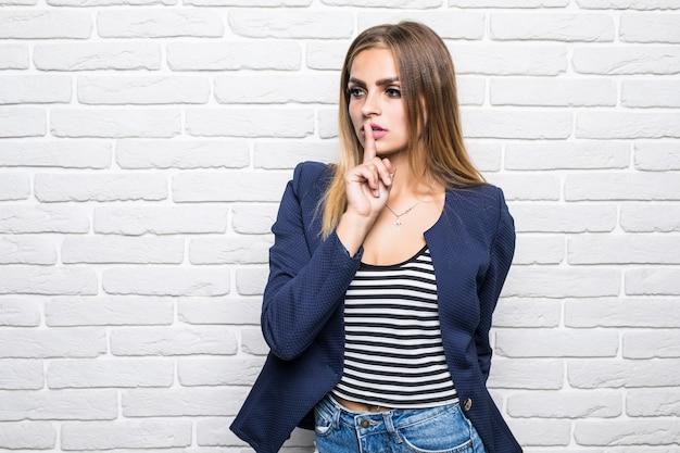 Młoda kobieta pokazuje znak zamknięcia usta i gest ciszy wkładając palec w usta na białym murem