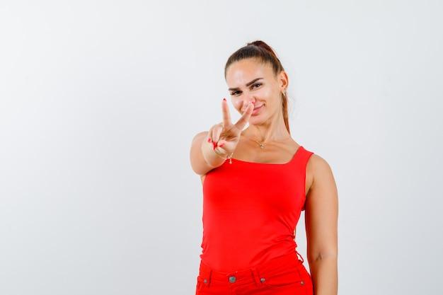 Młoda kobieta pokazuje znak zwycięstwa w czerwonym podkoszulku bez rękawów i wygląda błogo, widok z przodu.