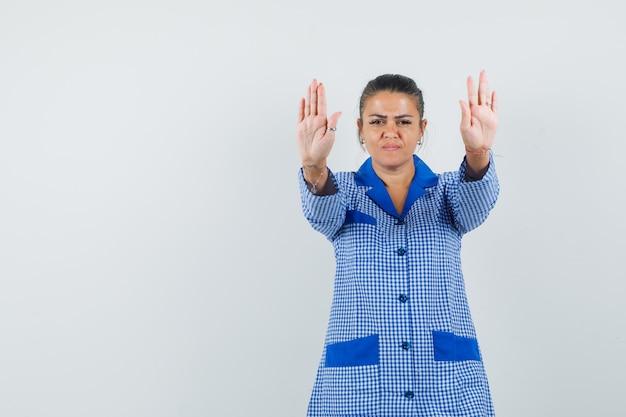 Młoda kobieta pokazuje znaki stop obiema rękami w niebieskiej koszuli od piżamy w kratkę i wygląda poważnie, widok z przodu.