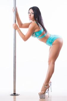 Młoda kobieta, pole dance, robi gimnastykę na białym tle