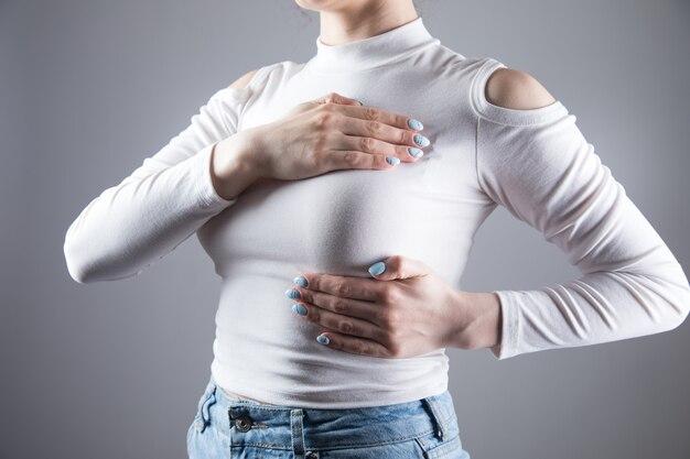 Młoda kobieta położyła dłoń na piersi na szarej scenie