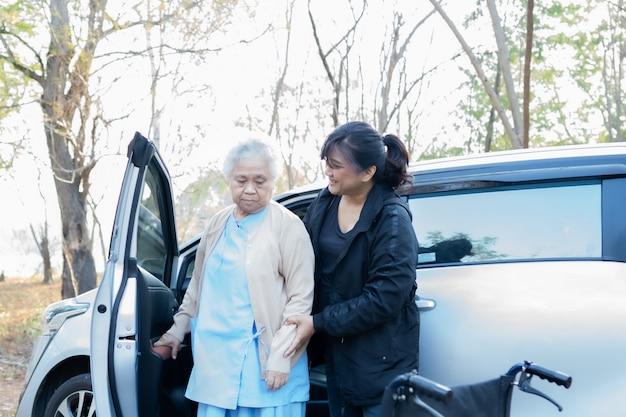 Młoda kobieta pomaga starszego pacjenta na wózku inwalidzkim