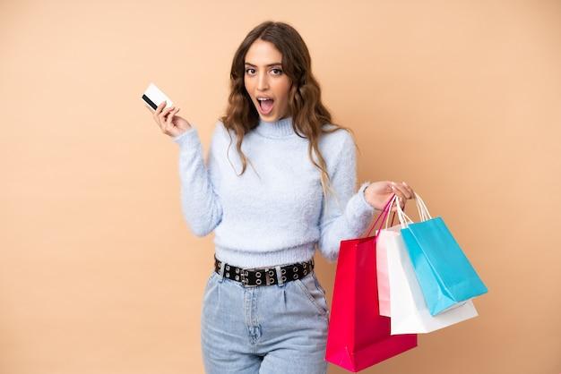 Młoda kobieta ponad ścianę trzymając torby na zakupy i zaskoczony