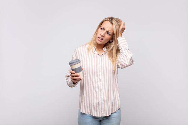 Młoda kobieta popijająca kawę zdziwiona i zdezorientowana, drapiąca się po głowie i spoglądająca w bok